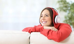 Happy female on couch with over ear headphones on