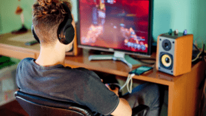 boy with gaming headset looking at his computer